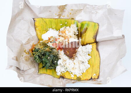 Nasi lemak ikan tuna bungkus, a traditional Indonesian Fried Spicy tuna with Rice and vegetables - Stock Photo