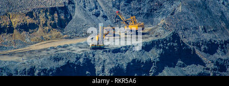 loading of mined iron ore in a pit to excavators in a cargo diesel dump truck.Summer season. Web banner. - Stock Photo
