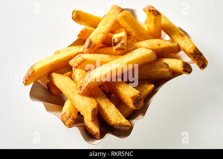 Portion of freshly made pommes frites or French fried potato chips in a dish isolated on white viewed high angle close up for advertising - Stock Photo