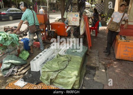 Breaking ice blocks with machine on the street in Phnom Penh - Stock Photo
