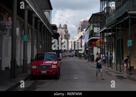 Bourbon Street in the French Quarter of New Orleans, Louisiana, United States of America. Urban view of American city with old buildings and people - Stock Photo
