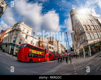 London, UK - February 11, 2019: British architecture on Oxford street in the main center area of London, with traditional red buses transporting touri - Stock Photo