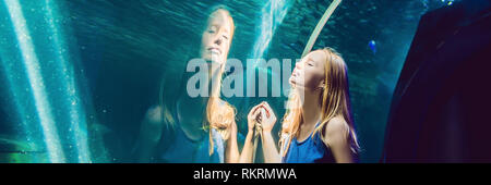 Young woman looking at fish in a tunnel aquarium BANNER, long format - Stock Photo