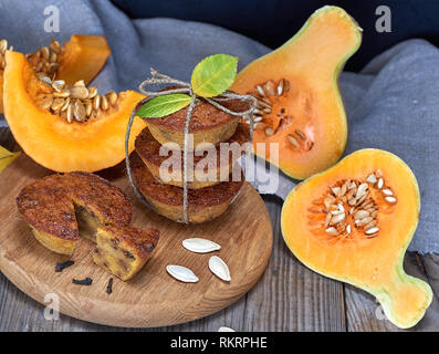 stack of muffins with a pumpkin on a round wooden board and fresh pieces of pumpkin - Stock Photo