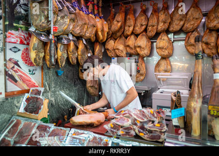 A butcher slices Jamón serrano, dry-cured Spanish ham, on his market stall inside the Central Market, Mercado Central, in Valencia, Spain. - Stock Photo
