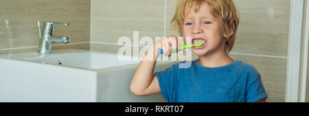Little blond boy learning brushing his teeth in domestic bath. Kid learning how to stay healthy. Health care concept BANNER, long format - Stock Photo