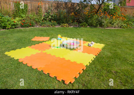 Color children's mat on the green grass in the country close-up. Handmade sandpit. Porous orange foam mat carpet. Children's shoes in the foreground.  - Stock Photo