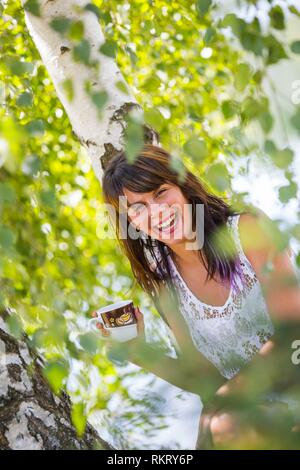 Attractive teenager girl is drinking coffee in nature looking at camera laughing extreme happy and smiling giggle giggling expressive expression - Stock Photo
