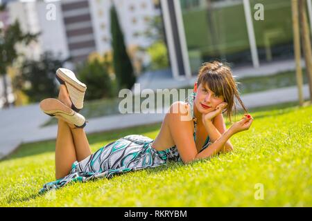 Young woman legs heels lying on stomach tummy belly on greenfield in park looking at camera - Stock Photo