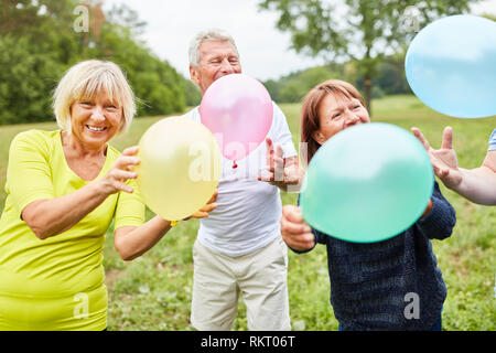 Happy seniors as friends with balloons celebrate birthday together - Stock Photo