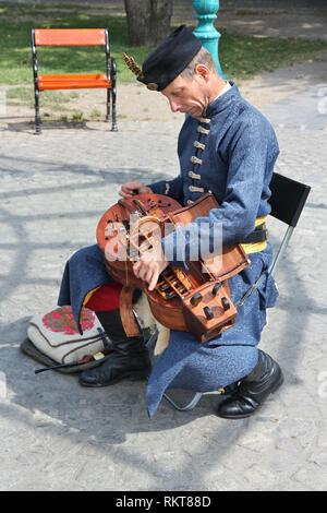 BUDAPEST, HUNGARY - JUNE 20, 2014: Street performer plays hurdy-gurdy in Budapest. Hurdy-gurdy is a traditional string instrument also known as wheel  - Stock Photo