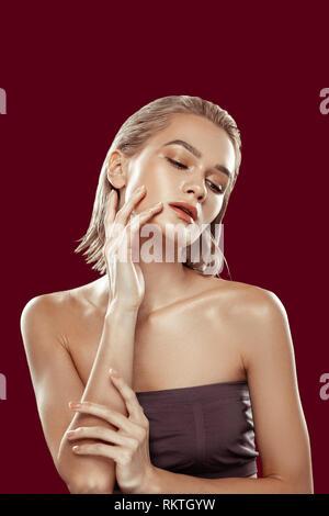 Photo model wearing open shoulders top working in photo studio - Stock Photo