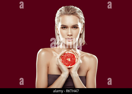 Beautiful photo model working while posing with grapefruit - Stock Photo