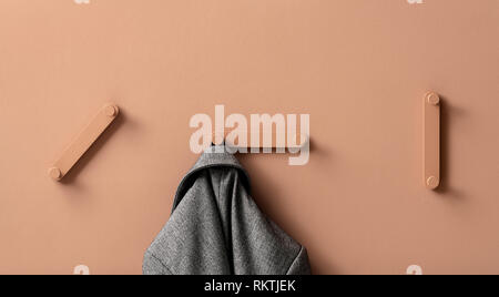 Fancy coral metal hangers with hanging gray jacket on colorful wall in studio - Stock Photo