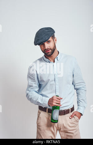 Bad boy. Bearded brutal man in hat holding a beer and looking ar camera while standing against grey background. Close up - Stock Photo