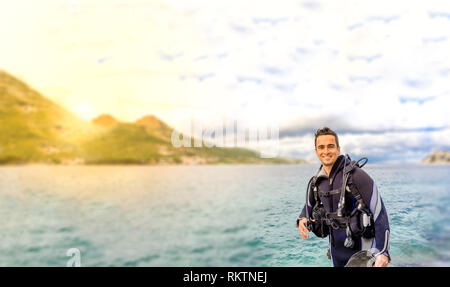 Young handsome man isolated diver smiling ready to go scuba diving in cold water wet suit, fins, weight belt & oxigen gear in Karaburun, Izmir. Turkey - Stock Photo
