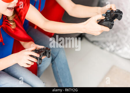Cropped view of woman and kid playing video game - Stock Photo