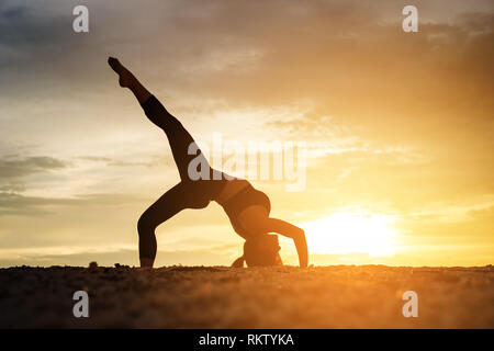 Young healthy woman practicing yoga on the beach exercise at sunset time. healthy concept. - Stock Photo