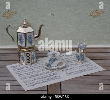 English teacup and saucer, silver-plated teapot on a silver stove, spoon vase and teaspoon, with floral decor, on a sheet of music - Stock Photo