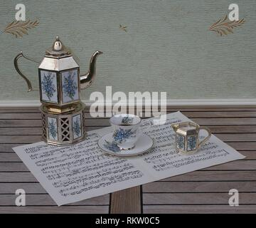 English teacup and saucer, silver-plated teapot on a silver stove and cream jug with floral decor on a sheet of music - Stock Photo
