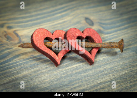 Two wooden hearts connected together with small rusted nail. Cut out wooden heart shapes painted red, viewed in close-up on wooden background with cop - Stock Photo