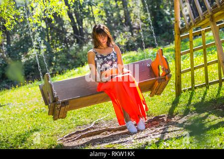 Pastoral scenery countrygirl reading book sitting on wooden bench in park charm charming picturesque - Stock Photo