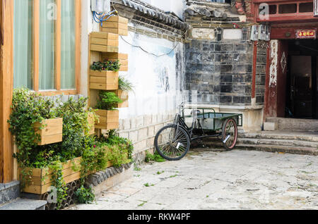 Bike near planters in the streets of Lijiang old town, Yunnan, China - Stock Photo