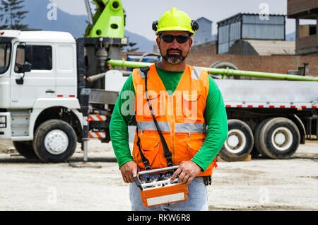 Concrete pump operator with remote control for boom pump truck at construction site. - Stock Photo
