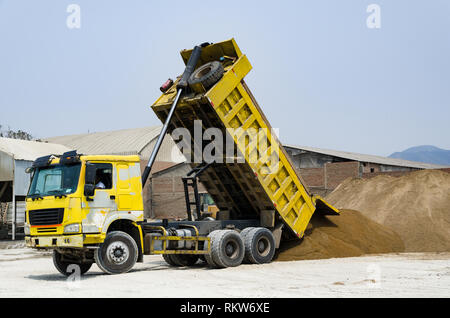 Ten yard dump truck delivering a load of dirt for a fill project at a new commercial development construction project - Stock Photo