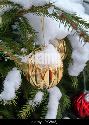 Closeup of snow covered Christmas tree bauble decorations on an outdoor Christmas tree. - Stock Photo