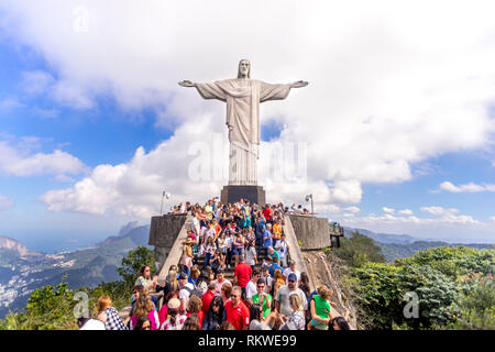 Clear view of a crowd of tourists on top of the Corcovado mountain in Rio de Janeiro with the Christ statue towering over them and a cloud behind - Stock Photo