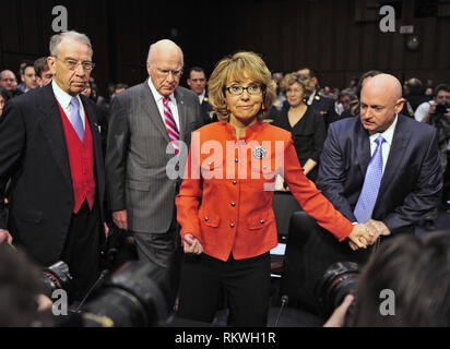 January 30, 2012 - Washington, District of Columbia, U.S. - Captain Mark Kelly, United States Navy (Retired), representing Americans for Responsible Solutions, right, leads his wife, former U.S. Representative Gabrielle Giffords (Democrat of Arizona), right center, to the witness table to read a statement before U. S. Senate Committee on the Judiciary hearing entitled ?What Should America Do About Gun Violence?? on Capitol Hill in Washington, DC on Wednesday, January 30, 2013. U.S. Senator Chuck Grassley (Republican of Iowa), left, the Ranking Member, and Chairman Patrick Leahy (Democrat of - Stock Photo
