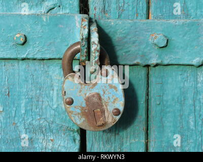 Old rusty padlock on green wooden doors. Locked gates, home security concept - Stock Photo