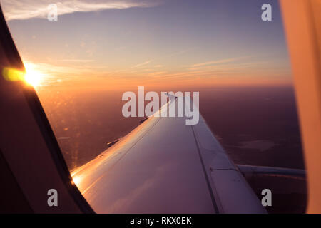Passenger POV View Through Airplane Window, Sunrise Above The Clouds Aerial - Stock Photo