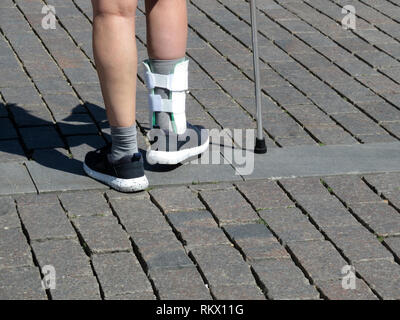 Female feet with the splint, orthosis for leg. Person with cane walking after a broken or sprain legs. Orthopedic orthosis for immobilizing foot - Stock Photo