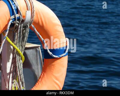 Orange life ring on the beach, water safety. Lifebuoy on the sea coast - Stock Photo