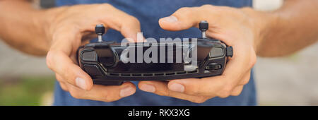 Man holds remote controller with his hands and controls the drone. New technologies and innovations concept BANNER long format - Stock Photo