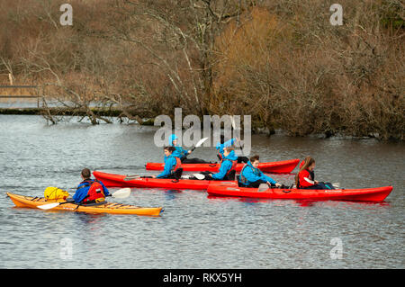 Group of teenagers young girls and an instructor enjoying canoe kayak paddling on a lake. Adventurous amateur paddlers canoeing kayaking activity. - Stock Photo