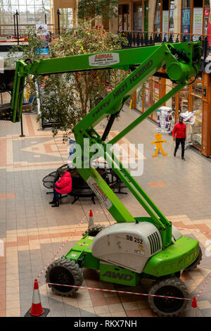 Green telescopic boom type lift access platform indoors. Aerial platform positioned indoors in public surrounding. - Stock Photo