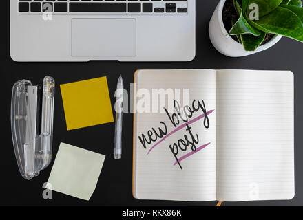 words new blog post written on note pad on desk next to laptop and adhesive notes - Stock Photo