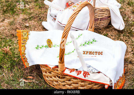 Ukrainian Orthodox Easter blessing wicker straw baskets with nobody on grass ground outside at church with generic religious sign text - Stock Photo