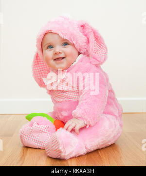Little cute baby in a pink Bunny suit. The child sits on the wooden floor. - Stock Photo