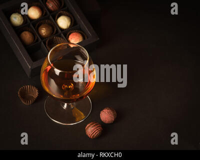 A glass of brandy and chocolate candy on a dark background. Alcoholic drink and elite chocolate food concept.