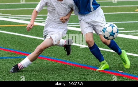 Two male soccer players are fighting for the ball during a soccer game. One is in a white uniform and tho other is in a blue top and white shorts. - Stock Photo