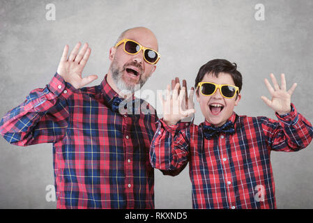 Father's day,father and son with tie and sunglasses on gray background - Stock Photo