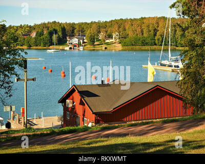 View over a Baltic Sea channel with sailing boats from the coast at Mariehamn in Aland, Finland, to woods with autumn foliage and elegant houses - Stock Photo