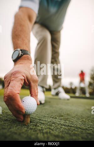 Close up of senior golfer hand placing the golf ball on tee at golf course driving range. Mature male golf player placing golf ball on tee at green. - Stock Photo