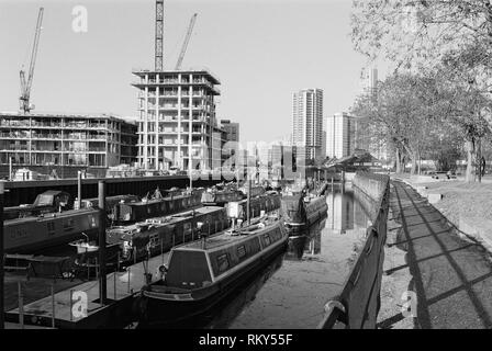 Narrowboats moored on Three Mills Wall River, Bromley-By-Bow, East London UK, looking towards Stratford, with new apartments under construction - Stock Photo