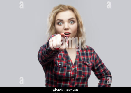 Portrait of amazed beautiful blonde young woman in casual red checkered shirt standing, pointing and looking at camera with unbelievable face. indoor  - Stock Photo