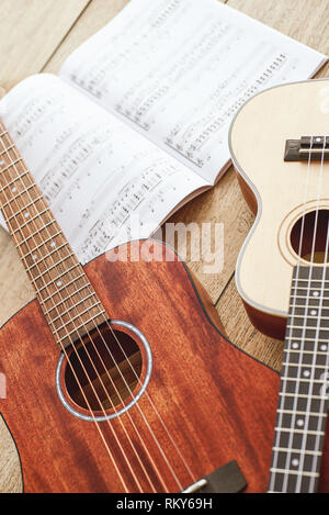 Learning how to play guitar. Vertical close up photo of acoustic and ukulele guitars lying on the wooden floor with music notes. Top view. Music equipment. Music shop. Musical instruments - Stock Photo